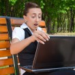 Amazed oung woman with laptop sitting on bench — Stock Photo