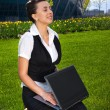 Young woman sitting on lawn with laptop — Stock Photo