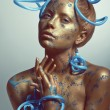 Woman with golden body-art and blue tubes — Stock Photo