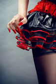 Female in black and red fetish skirt on blue background — Stock Photo