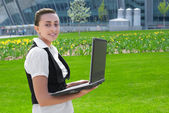 Smiling young woman holding laptop — Stock Photo
