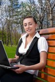 Young smiling woman sitting on bench with laptop — Stock Photo