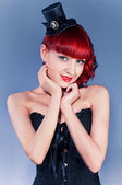 Studio portrait of young woman in little hat and corset in pin-up style — ストック写真