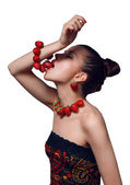 Studio portrait of young beautiful woman eating strawberry bracelet isolated on white — ストック写真