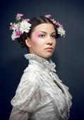 Młoda piękna kobieta w białej bluzce i kwiaty — Zdjęcie stockowe