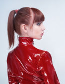 Studio portrait of youg beautiful woman in red PVC jacket — Stok fotoğraf