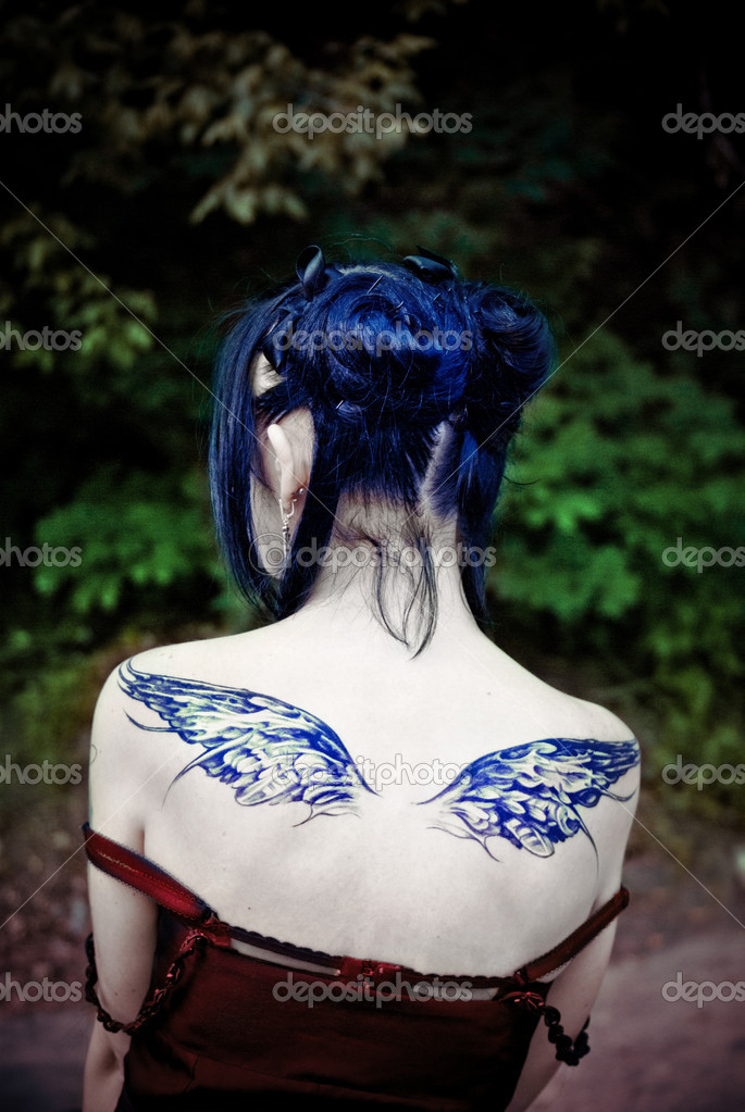 Portrait of young beautiful woman with tattoo of wings on her back — Stock Photo #10240925