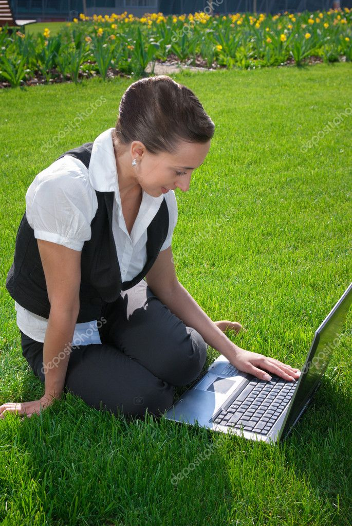 Young woman sitting on lawn with laptop  Stock Photo #10241157