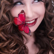 Stockfoto: Redhead curly woman with red butterfly on lips