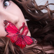 Redhead curly woman with red butterfly on lips — Stock Photo