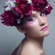 Studio portrait of young woman with peony in head — Stock Photo