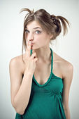 Studio portrait of surprised girl in green outfit with pigtails — Stock Photo