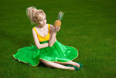 Girl with pineapple sitting on lawn — Stok fotoğraf
