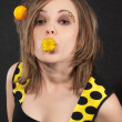 Studio portrait of funny young women with yellow balls in hair on black background — Stock Photo