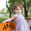 Royalty-Free Stock Photo: Little girl standing on bench in park