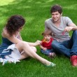 Happy family with little daughter sitting on green grass in park — Foto Stock