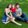 Happy family with little daughter sitting on green grass in park - ストック写真