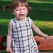 Little crying girl in park — Stockfoto