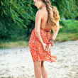 Stock Photo: Beautiful girl in orange dress on beach
