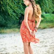 Beautiful girl in orange dress on beach — Stock Photo