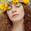 Studio portrait of young beautiful woman with flowers in hair — Stock Photo