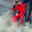 Young man in red overall in industrial style sitting on rusty ladder - Foto Stock