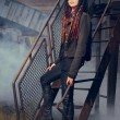 Young woman in industrial style standing on stairs - Foto Stock