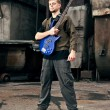 Young musician with guitar in industrial style - Foto Stock