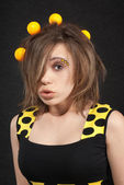 Studio portrait of funny young women with yellow balls in hair on black background — ストック写真