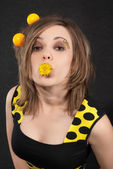 Studio portrait of funny young women with yellow balls in hair on black background — Stok fotoğraf