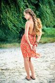 Beautiful girl in orange dress on beach — Stock Photo