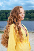 Portrait of young long-haired attractive woman in yellow outfit on river beach — Stok fotoğraf