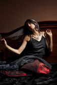 Krásná mladá žena v černé a červené šaty sedí na posteli — Stock fotografie