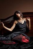 Mulher jovem e bonita de vestido preto e vermelho, sentada na cama — Foto Stock