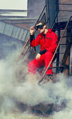Young man in red overall in industrial style sitting on rusty ladder — Stok fotoğraf