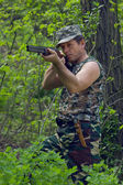 Hunter in forest with gun in hands — Stock Photo