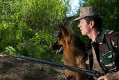 Hunter with dog and rifle. Ambush — Stock Photo