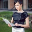 Portrait of young business woman holding netbook — Stockfoto