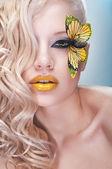 Blonde lockige frau mit gelben schmetterling auf wimpern — Stockfoto