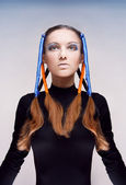 Studio portrait of young woman with blue and orange ribbons in hair — Stok fotoğraf