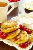 Cheese pancake with sour cream and red currant — Stock Photo