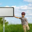 Boy cyclist leaning on blank sign — Stock Photo