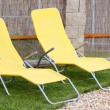 Stock Photo: Two empty yellow sun loungers on garden