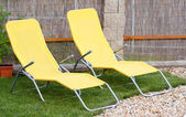 Two empty yellow sun loungers on a garden — Stock Photo
