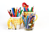 Pen holders with colored pens on a white background — Stok fotoğraf