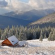 Small house of hunters on a winter hillside — Stock Photo