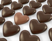 Heart shaped milk chocolate candy between dark ones — Stock Photo