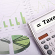 Tax or taxes concept with business calculator - Stock Photo