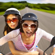 Stock Photo: Two girls riding scooter on the road