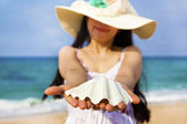 Smiling young woman holding shell on the beach — Stock Photo